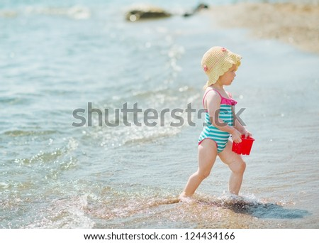Baby playing with pail on seashore - stock photo