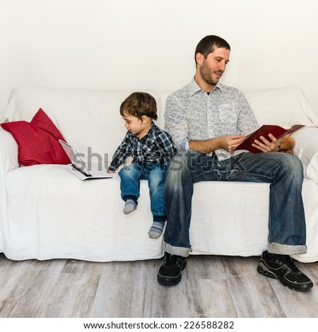 Baby playing with tablet and father reading a book on a white sofa - stock photo