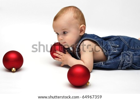 baby playing with the Christmas glass ball on the white background - stock photo