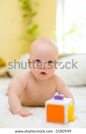 Baby playing with toy on bed - stock photo