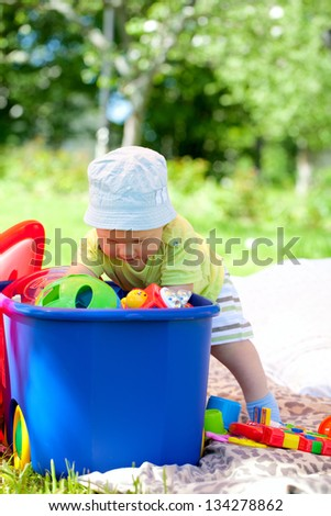 baby playing with toys in garden