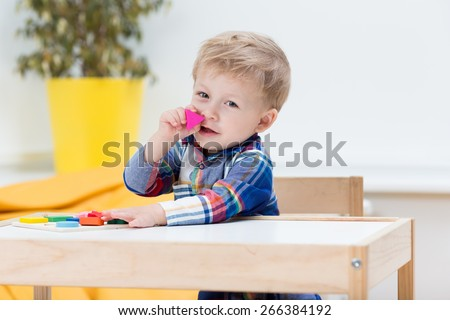 Baby playing with wooden geometry block puzzle.  - stock photo