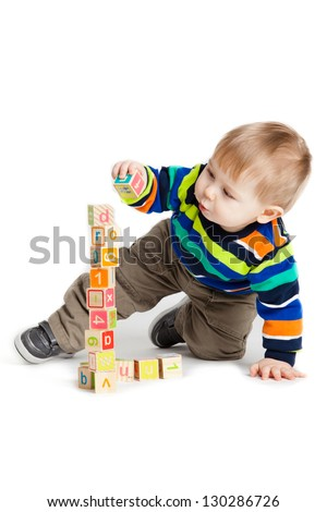 baby playing with wooden toy cubes with letters. Wooden alphabet blocks. - stock photo