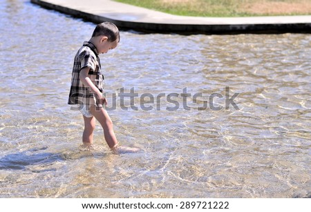 Baby plays water in the park - stock photo
