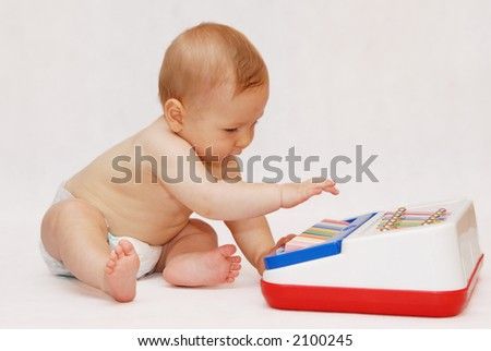 Baby portrait with piano toy - stock photo
