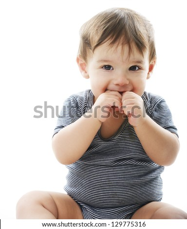 Baby putting his hands and fingers into mouth - stock photo