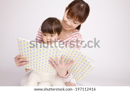Baby Reading A Book To His Mother - stock photo