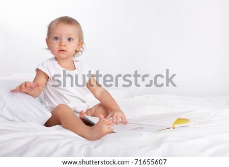 Baby reading book on the bed