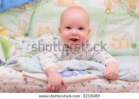 Baby rest on bed and look at camera #2 - stock photo
