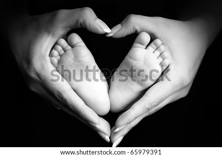 Baby's feet in mom's palms - stock photo