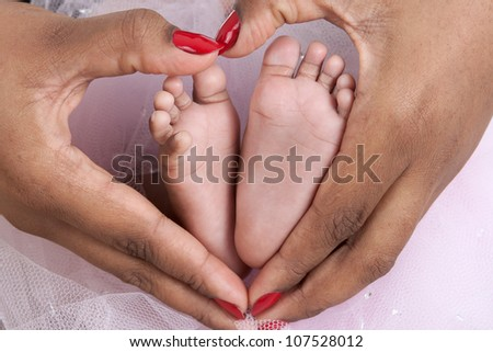Baby's feet in mom's palms, forming a heart shape with mother's hands. Candid appeal. - stock photo
