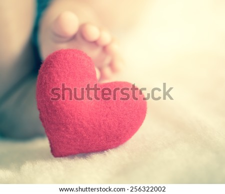 baby's feet with a red heart in vintage filtered style - stock photo