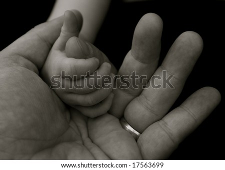 Baby's grip on a fathers hand - stock photo