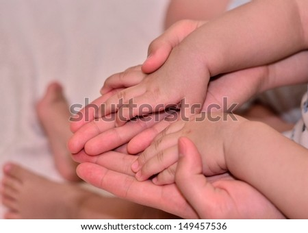 Baby's hand on top of mommy's hand - stock photo