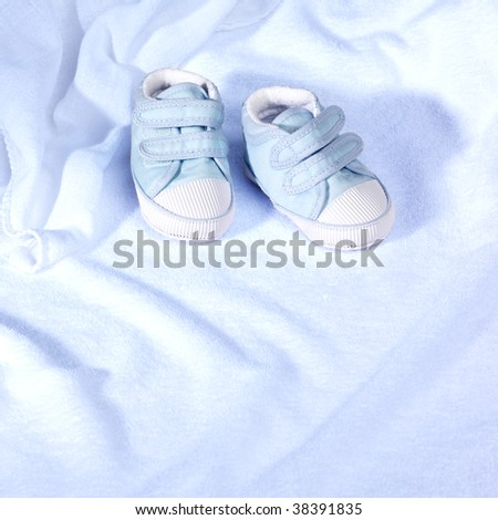 Baby's shoes on a towel - stock photo
