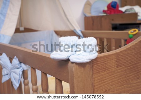 Baby shoes on a baby bed / children's room
