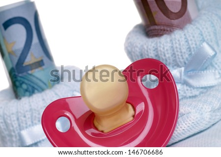 Baby shoes with baby teats and euro banknotes / Costs for a baby - stock photo