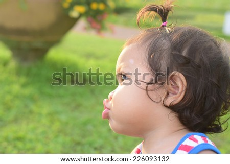baby show joker face when playing in garden - stock photo