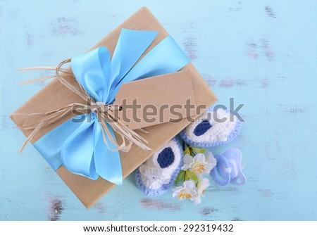 Baby shower Its a Boy natural wrap gift with gift box, baby booties and dummy on pale blue shabby chic rustic wood table.  - stock photo