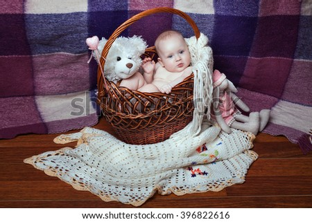 Baby sits in a basket with a toy bear. Toy bunny next to basket - stock photo
