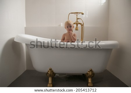 baby sitting an a bathtub with golden tap