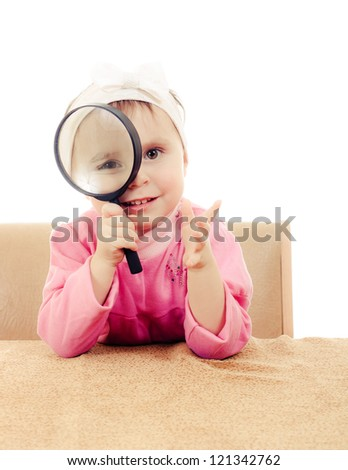Baby sitting at a table looking through a magnifying glass. - stock photo