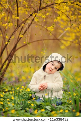baby sitting by a beautiful bush with yellow flowers. spring - stock photo