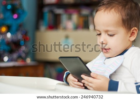 baby sitting in a high chair and looking at tablet - stock photo