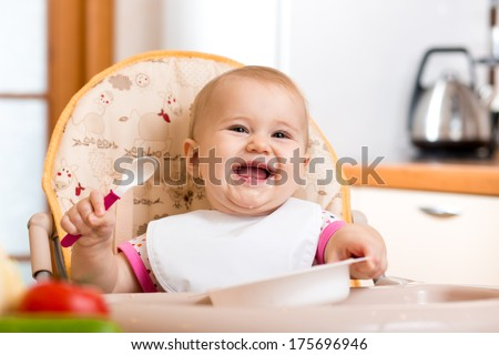 baby sitting in high-chair with spoon and plate on kitchen - stock photo