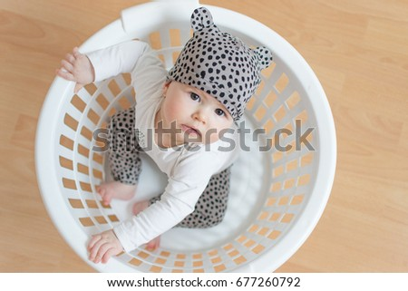 baby sitting in white basket looking up and dressed in leopard pattern photo taken from above