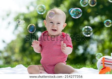 baby sitting on gras - stock photo