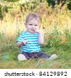 baby sitting on grass smiling - stock photo
