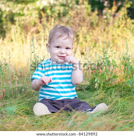 baby sitting on grass smiling