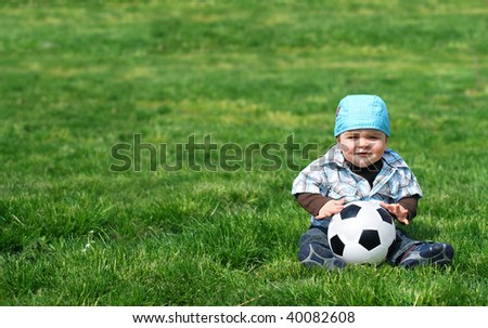 Baby sitting on green grass with a soccer ball