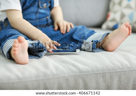 Baby sitting on sofa and playing with smartphone - stock photo