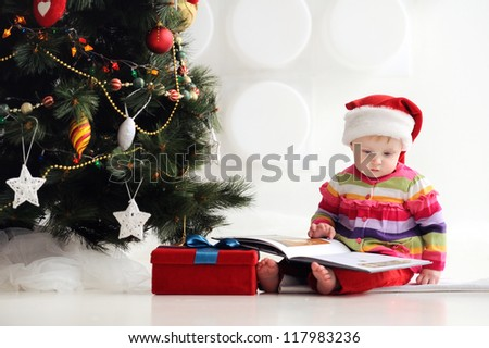 Baby sitting on the floor in a santa hat and reading a book. A child in a red cap. In the background, Christmas tree with ornaments. Christmas. The floor box with gifts. - stock photo