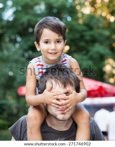Baby sitting on the neck of his father. Focus on the child eyes. Shallow DOF - stock photo