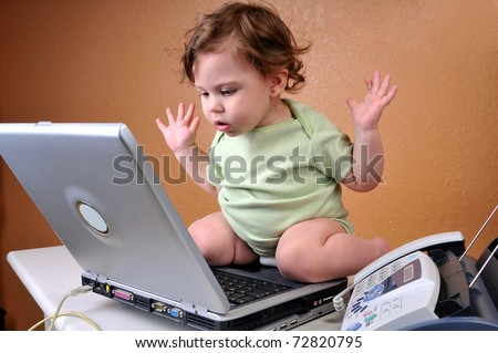 "Baby sitting on top of laptop looking confused with hands in the air as if to say ""What happened to the file?"" It disappears from the hard drive."