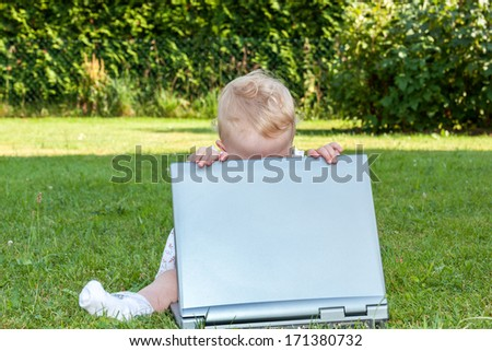 Baby sitting with laptop in a meadow - stock photo