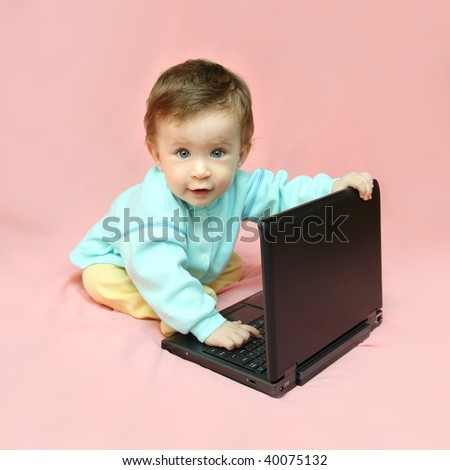 baby sitting with laptop on pink background - stock photo