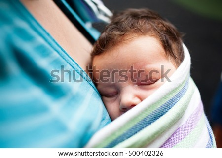 Baby sleeping against mothers chest in sling.