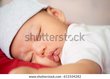 Baby sleeping in bed.Asian infant boy sleep in red bed sheet.