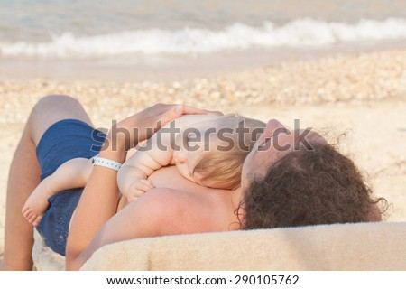 Baby sleeping on his father's chest on the beach near the sea. - stock photo