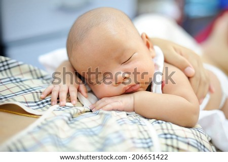 baby sleeping on the mother's chest. - stock photo
