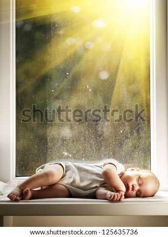 baby sleeping on white blanket on window - stock photo