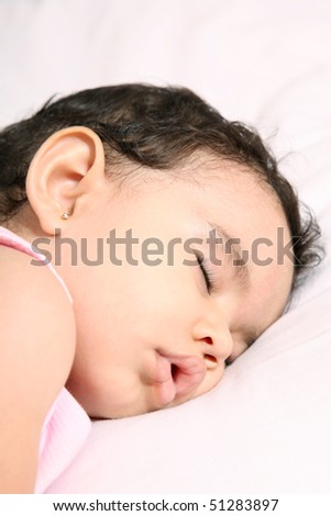 Baby sleeping on white blanket. one year old