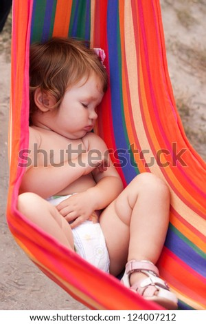 Baby sleeping peacefully in striped sling as hammock. Summer holiday. - stock photo