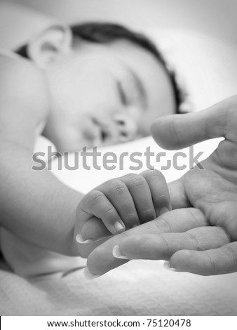 Baby sleeping take the hand of her mother in black and white - stock photo