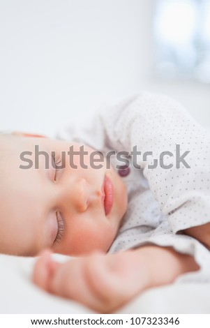 Baby sleeping while extending her arm in a bedroom - stock photo