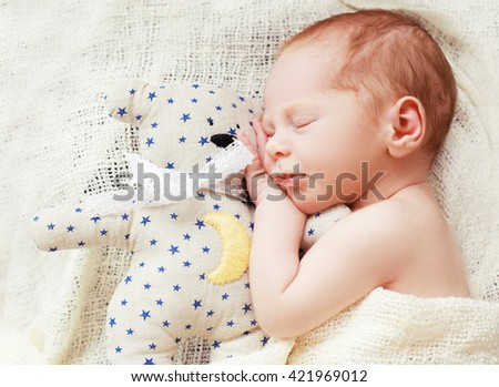 Baby sleeping with her teddy bear. New born relax in a white bedroom. Family at home. Love
